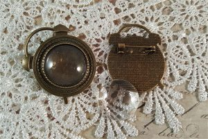 bronze clock brooches with glass cabochons